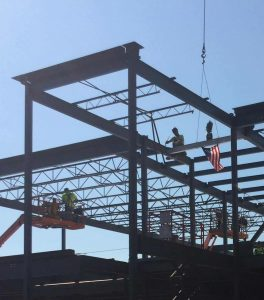 Steel workers secure the final beam into-place-