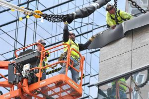 Ironworkers pull in the chains at the end of the net's structural rope to make connections at an attachment point. (Photo credit: Harry Brett)