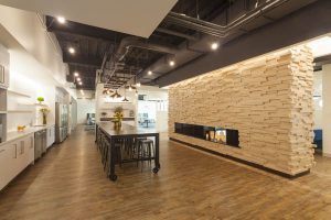 The main cafeteria area features a welcoming faux fireplace wall, an industrial oiled steel bar and restaurant-style seating areas.
