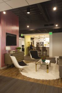 This collaboration zone highlights a contemporary living area, which features products available on the Wayfair.com website. Modern seating, a shag rug and pink houndstooth wallcovering warm up the office environment.