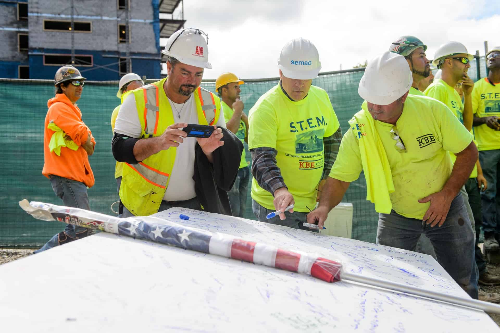 Construction workers sign a concrete panel that will be hoisted to the roof during the topping off ceremony for the STEM residence hall on Sept. 14, 2015. (Peter Morenus/UConn Photo)